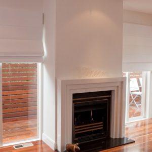 Roman Blinds - roman blinds installed on living room windows beside fireplace