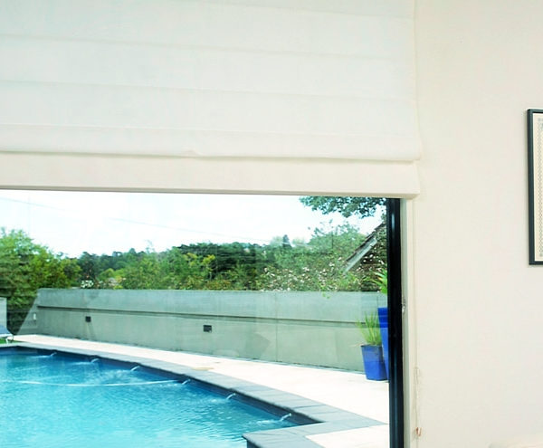 Roman Blinds - View of swimming pool through window with roman blinds installed