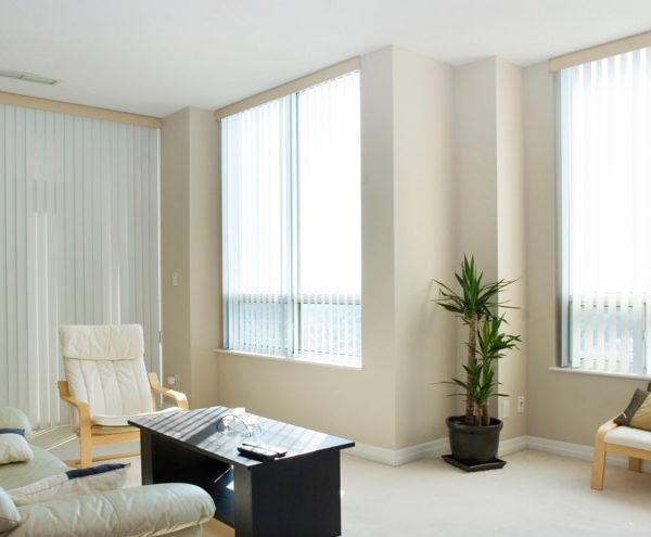 White vertical blinds installed on living room windows